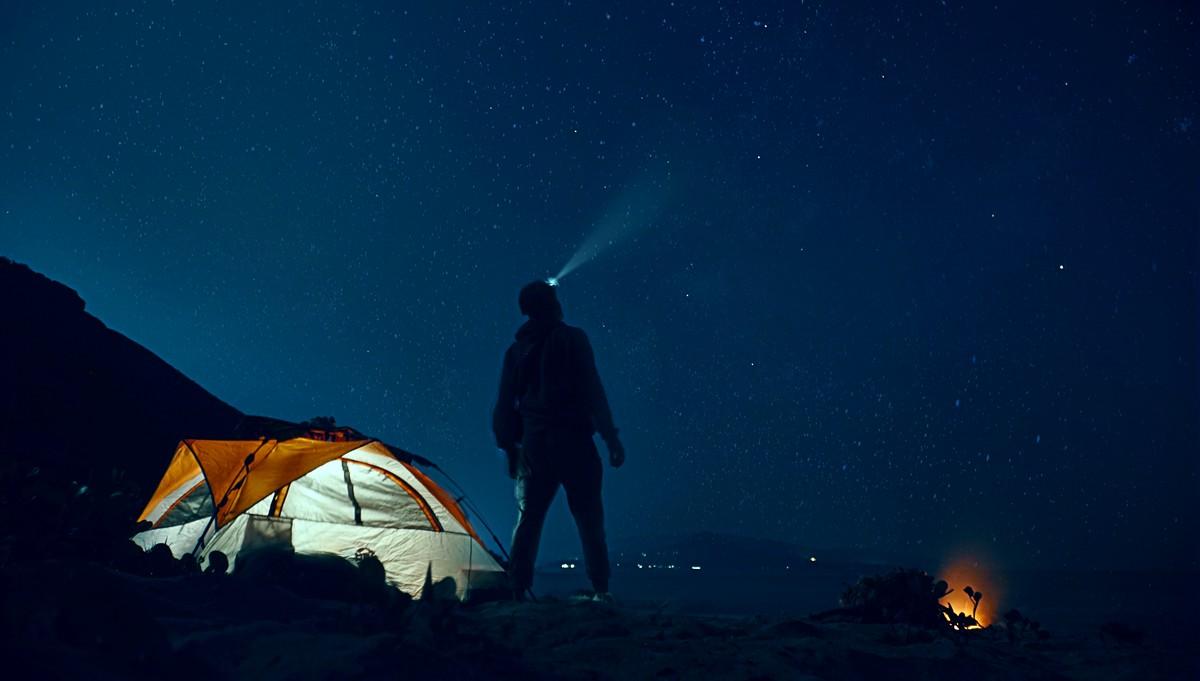 Muž stojí na kopci a zkouší noční vidění.
