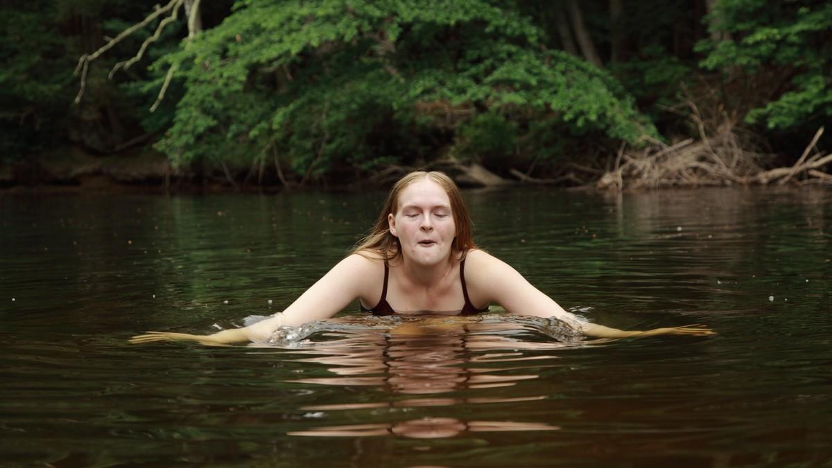 Dívka se věnuje otužování ve studené vodě.