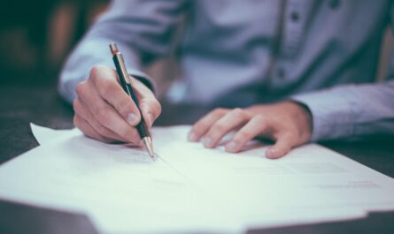 Klient podepisuje v bance refinancování hypotéky.
