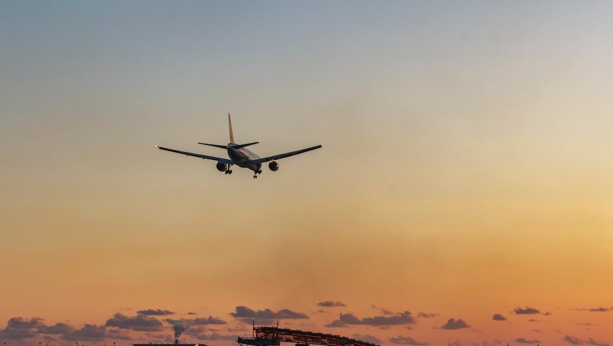 Obří letadla vznášející se v oblacích při západu slunce.